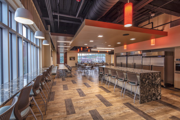 Communal cafeteria in the new Tompkins Financial Corporation Headquarters features marble countertops and bars, industrial fridges and lots of seating. The space is decorated with tan and brown geometric patterned floors, red and white pendant lights, and an industrial feel with unfinished, dark ceilings.