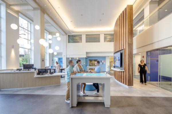 A 2 story bank lobby with bright white walls, gray tile floors, sky blue and wooden accents and decorated with modern furniture is inclosed by 2 floors of offices, and is illuminated by large pane windows and an array of hanging globe lights. CFCU Community Credit Union is focused on an immersive and technology rich banking experience, iPads, computers and touch displays are available to customers throughout the renovated historic banking lobby.