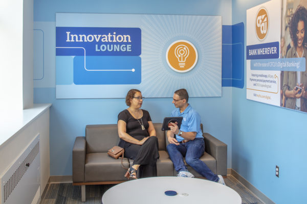 The innovation lounge in the downtown Ithaca CFCU Community Credit Union Transformation Center is a nook in the main banking hall, painted sky blue and made comfortable with a couch and round white table. A customer is receiving help from bank staff, seated comfortably and utilizing the new technology the bank implemented.