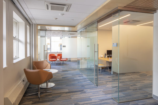 A view of 2 full glass executive corner offices, and the hallway between them, which has a modern tan chairs and a small table.