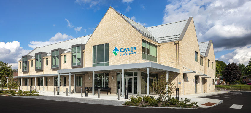 Exterior shot of the Cayuga Medical Offices At Community Corners located at 903-909 Hanshaw Road, featuring 28,000sf, 3 story a tan brick façade with a steep gabled roof, and large modern windows fits seemingly into a mixed-use residential neighborhood. Adjacent to Gimme! Coffee, The Heights Restaurant, & Chemung Canal Trust Company and across the street from The Sunoco Gas Station; this on-stage/off-stage model includes 6 distinct pods or regions to house six to eight exam rooms each. Photographed on a sunny summer day, the entrance features a modern steel awning with black benches and planters spilling into an ample parking lot.