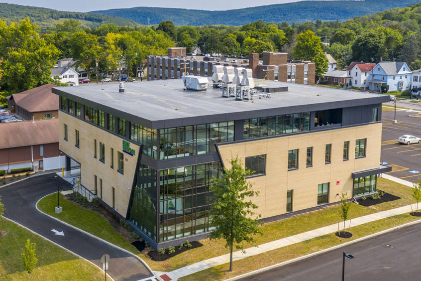 A birds eye view of the new stand alone building housing the corporate headquarters for First Heritage Federal Credit Union located in Corning New York. The 3 story building has a 2 story glass and steel angular volume on the east corner revealed from behind tan masonry facade, many large punched windows all floors, and full height glass windows creating the exterior enclosure for the entire top floor. The building sits atop a well manicured lawn, with a large parking lot in back, a one way drive-through for teller lanes, and a parking lot access road in front.