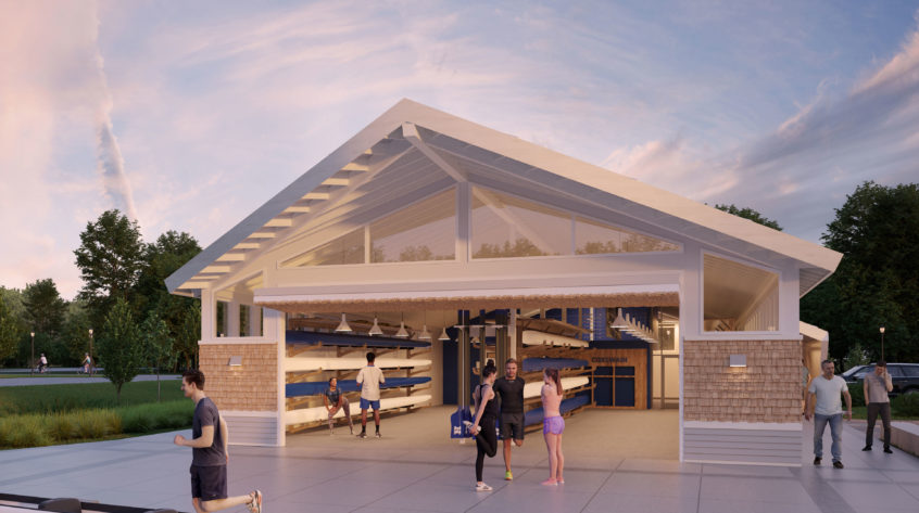 An exterior to interior view of the new Hamilton Boathouse rowing center, with an elaborate peaked roof which covers a communal patio area, full of students exercising. The inside of the boat house is visible through doors that open the entire end of the building, showing wooden boat racks along the walls. The building has a white, warm tan, and light grey facade with the white metal and beam roof extending beyond the walls to create a canopy along all sides of the building.